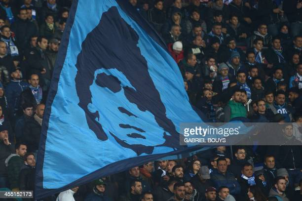 Napoli's fans wave a giant flag showing former Argentinian soccer star Diego Maradona prior the UEFA Champions League group F football match between...