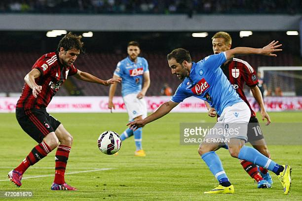 Napoli's forward from Argntina and France Gonzalo Higuain fights for the ball with Milan's midfielder from Italy Andrea Poli and Milan's forward from...