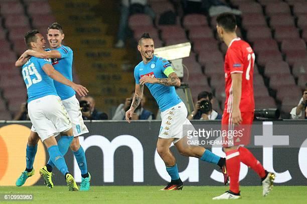 Napoli's forward from Poland Arkadiusz Milik celebrates with teammates Napoli's midfielder from Brazil Jorginho and Napoli's midfielder from Slovakia...
