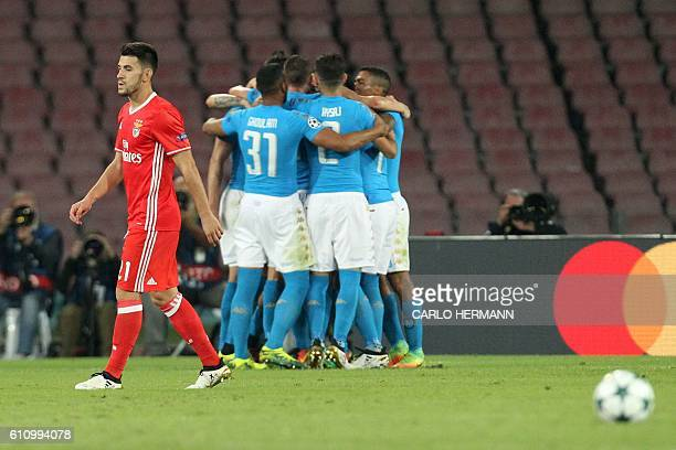 Napoli's forward from Poland Arkadiusz Milik celebrates with teammates after scoring a penalty as Benfica's midfielder Pizzi looks dejected during...