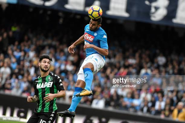 Napoli's French defender Faouzi Ghoulam jumps for the ball next to Sassuolo's midfielder from Italy Matteo Politano during the Italian Serie A...