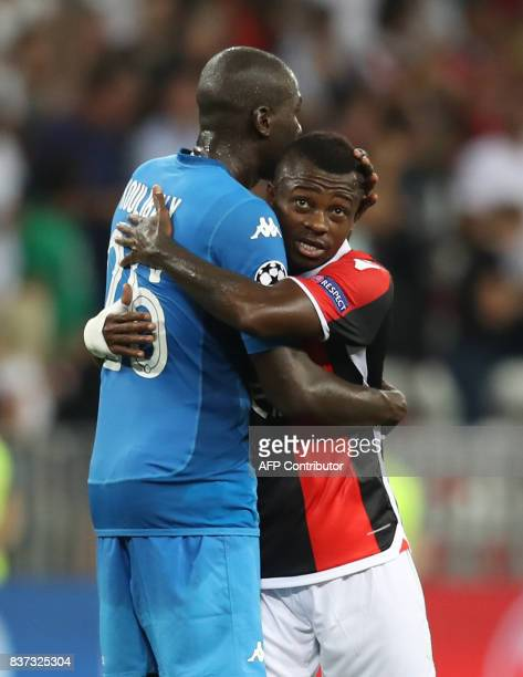 Napoli's French defender Kalidou Koulibaly hugs Nice's Ivorian midfielder Jean Michael Seri after the UEFA Champions League playoff football match...