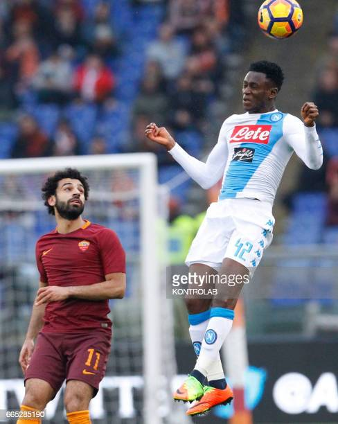 Napoli's Guinean midfielder Amadou Diawara heads the ball near Roma's Egyptian forward Mohamed Salah during the Italian Serie A football match AS...