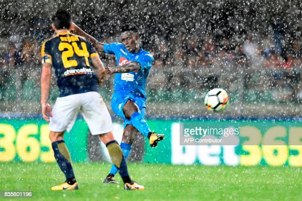 Napoli's Guinean midfielder Amadou Diawara kicks the ball past Hellas Verona's Brazilian midfielder Daniel Bessa during during the Italian Serie A...