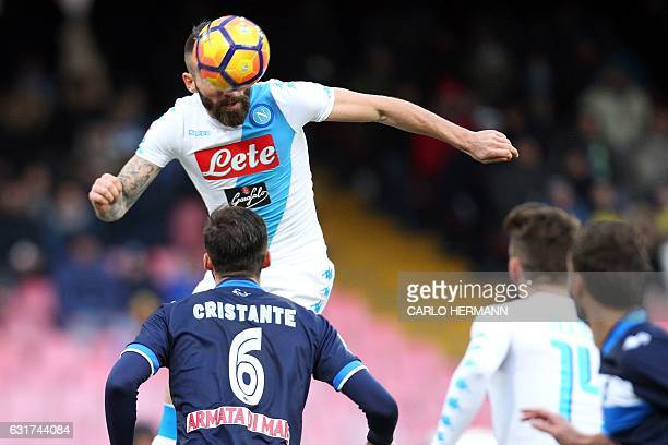 Napoli's Italian defender Lorenzo Tonelli heads the ball and scores during the Italian Serie A football match between SSC Napoli and Delfino Pescara...