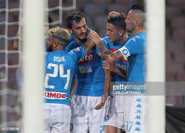 Napoli's Italian forward Manolo Gabbiadini is congratulated by teammates after scoring a goal during the Italian Serie A football match SSC Napoli vs...