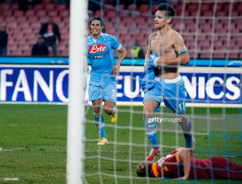 Napoli's Italian midfielder Christian Maggio (C) celebrates with teammate Uruguayan forward Edinson Cavani (L) as Roma's Italian defender Federico Balzaretti lies on the field during the Serie A football match SSC Napoli vs AS Roma in San Paolo Stadium on January 6, 2013, in Naples.