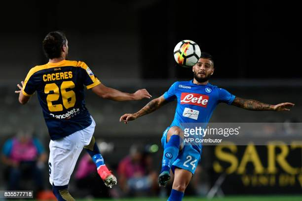 Napoli's Italian striker Lorenzo Insigne vies with Hellas Verona's Uruguayan defender Martin Caceres during during the Italian Serie A football match...