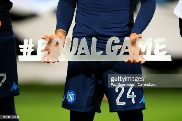 Napoli's Lorenzo Insigne holds a signs saying #equalgame as the team line up ahead of kickoff during the UEFA Champions League group F match between...