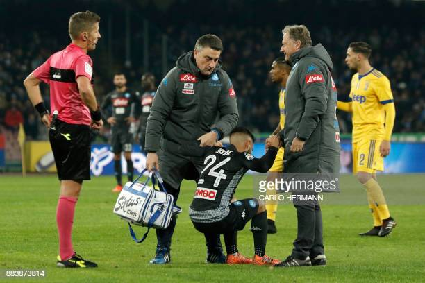 Napoli's midfielder from Italy Lorenzo Insigne is helped to get up during the Italian Serie A football match Napoli vs Juventus on December 1 2017 at...
