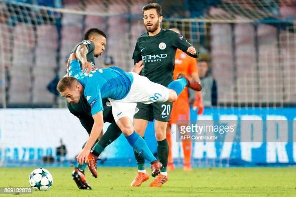 Napoli's midfielder Marko Rog fights for the ball with Manchester City's Brazilian striker Gabriel Jesus and Manchester City's Portuguese midfielder...
