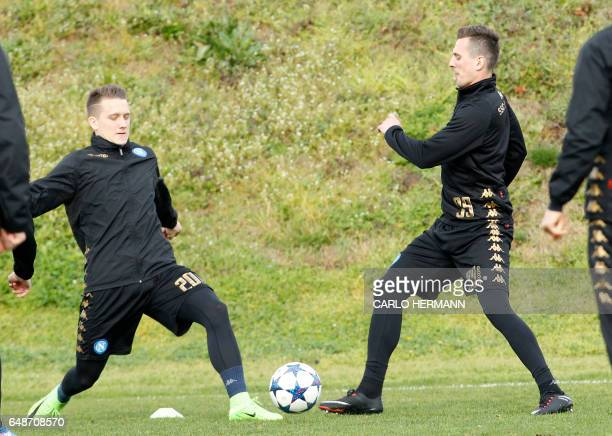Napoli's Polish forward Arkadiusz Milik fights for the ball with teammate Napoli's Polish midfielder Piotr Zielinski during a training session on the...