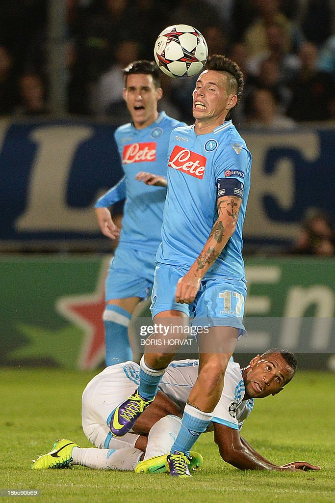 Napoli's Slovak midfielder Marek Hamsik (R) fights for the ball with Marseille's Togolese midfielder Jacques-Alaixys Romao (ground) on October 22, 2013 during a UEFA Champion's league Group F football match at the Velodrome stadium in the southern French city of Marseille.