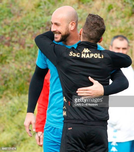 Napoli's Spanish goalkeeper Pepe Reina hugs teammate Napoli's Belgian forward Dries Mertens during a training session on the eve of the UEFA...