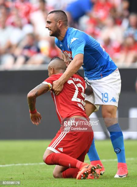Napoli's striker Lorenzo Insigne and helps Bayern Munich's Chilian midfielder Arturo Vidal after an attack during the third place Audi Cup soccer...