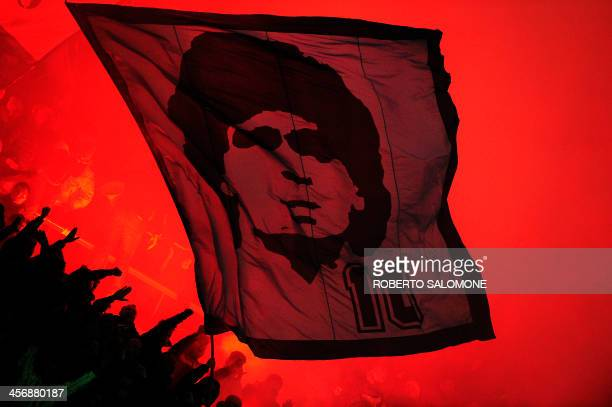 SSC Napoli's supporters wave a flag bearing a portrait of football legend Argentinian Diego Maradona during the Serie A football match SSC Napoli vs...