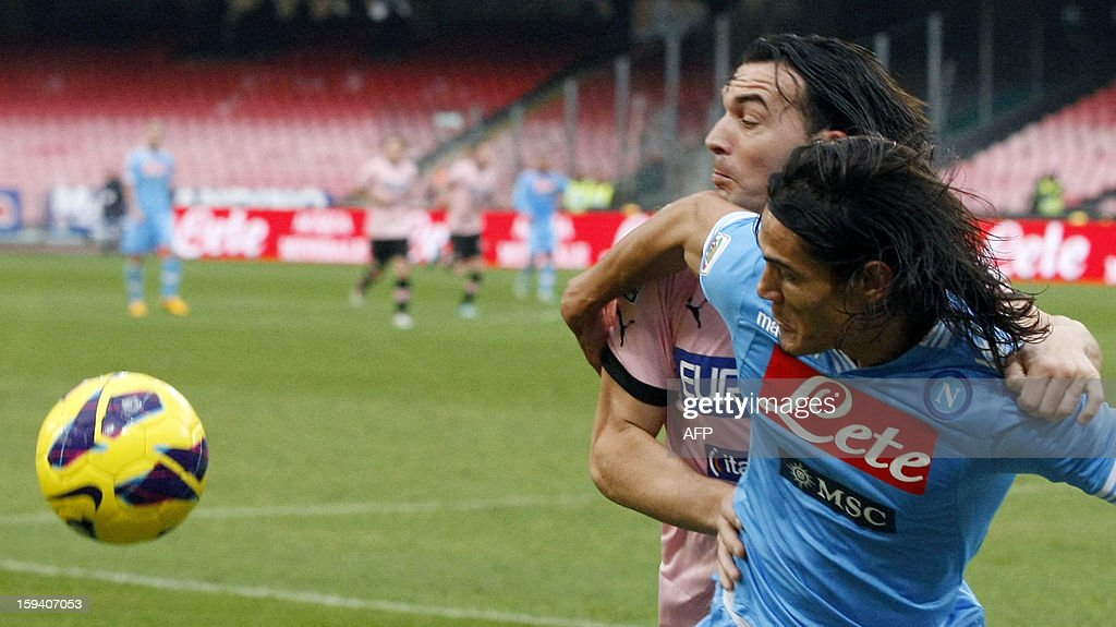 Napoli's Uruguayan forward Edinson Cavani (R) vies with Palermo's defender Salvatore Aronica during an Italian Serie A football match between SSC Napoli and USC Palermo in San Paolo Stadium on January 13, 2013.