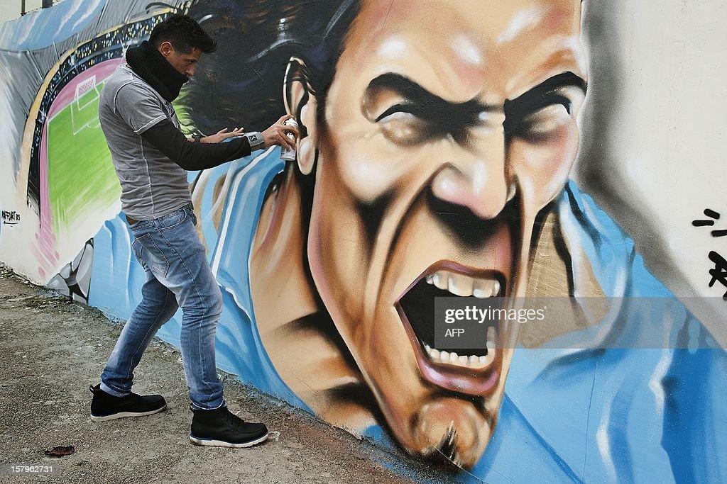 Napolitan artist Raffo works on a seven-meter mural pianting depicting SSC Napoli's Uruguayan forward Edinson Cavani on December 8, 2012 in Volla near Naples. Raffo is a well known street artist in Naples. AFP PHOTO/Anna Monaco
