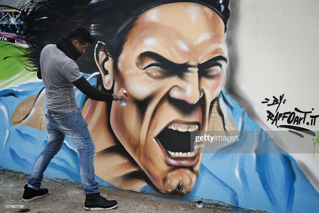 Napolitan artist Raffo works on a seven-meter mural pianting depicting SSC Napoli's Uruguayan forward Edinson Cavani on December 8, 2012 in Volla near Naples. Raffo is a well known street artist in Naples. AFP PHOTO/Anna Monaco