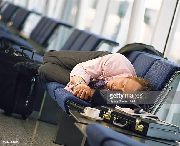 Napping businessman at airport
