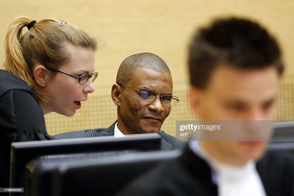 Narcisse Arido of the Democratic Republic of the Congo (C) listens to one of his lawyers during his first appearance in the courtroom of the International Criminal Court (ICC) in The Hague, The Netherlands, on March 20, 2014. Arido is suspected of offences against the administration of justice allegedly committed in connection with the case against opposition leader Jean-Pierre Bemba Gombo, consisting of corruptly influencing witnesses before the ICC and presenting evidence that he knew to be false or forged. AFP PHOTO / POOL / BAS CZERWINSKI -- The Netherlands out --