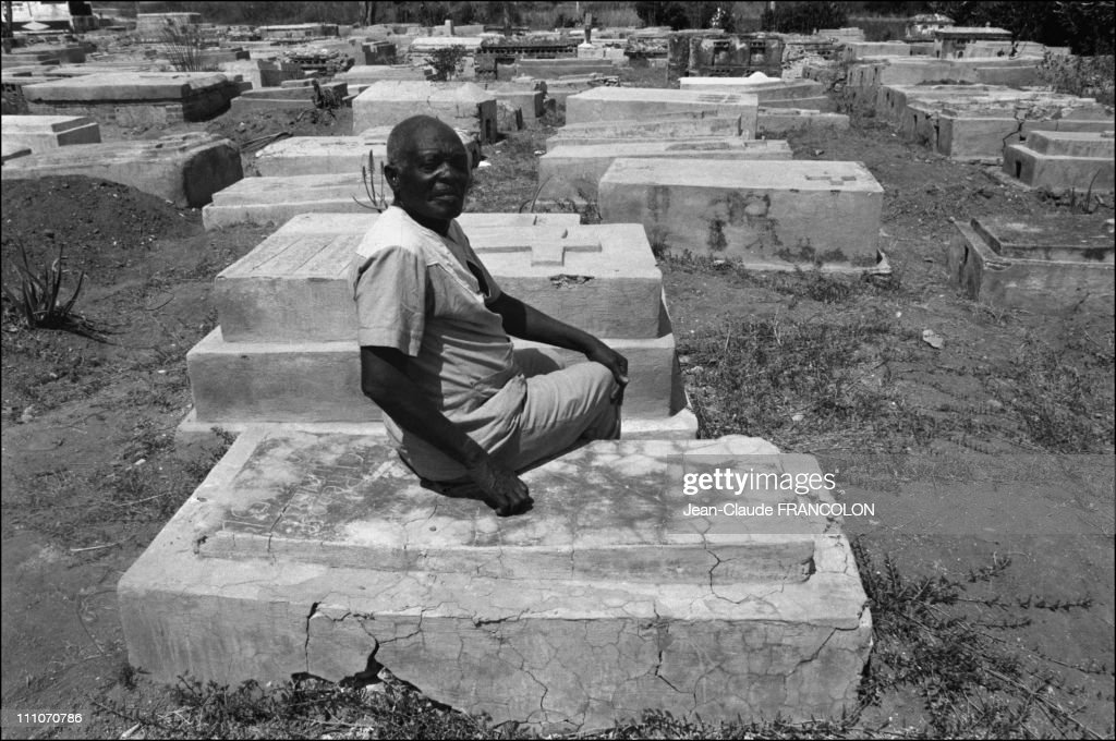Narcisse at the site where he was buried in may 1962 in Haiti - This man, called Clairvius Narcisse had been declared dead in Albert Schweitzer Hospital at 1:15 AM on May 2, 1962, and buried in l'Estere the next day, covered by a memorial slab ten days later - However, he returned to his village in 1980, where he met his sister Angelina, introducing himself with a name that only intimate family members had known - He claimed that he had been through zombification - A scar on his right cheek shows where a nail had hit him while being buried in Haiti in March, 1982.
