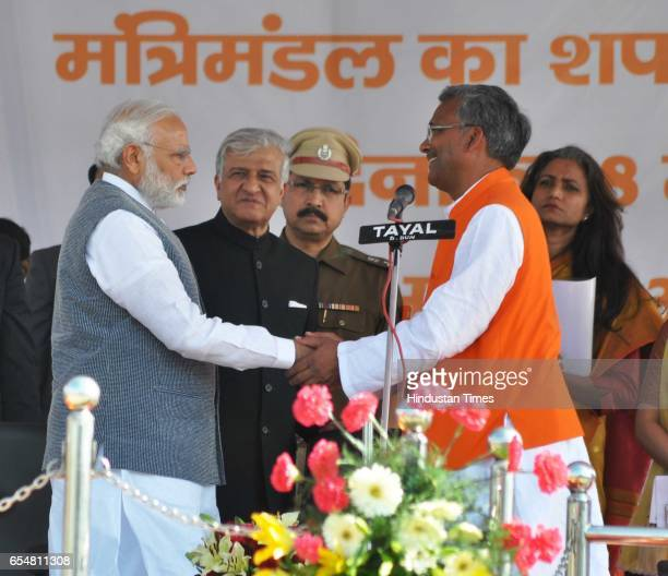 Narendra Modi greets the 9th CM of Uttarakhand Trivendra Singh Rawat during the swearingin ceremony at Parade Ground on March 18 2017 in Dehradun...