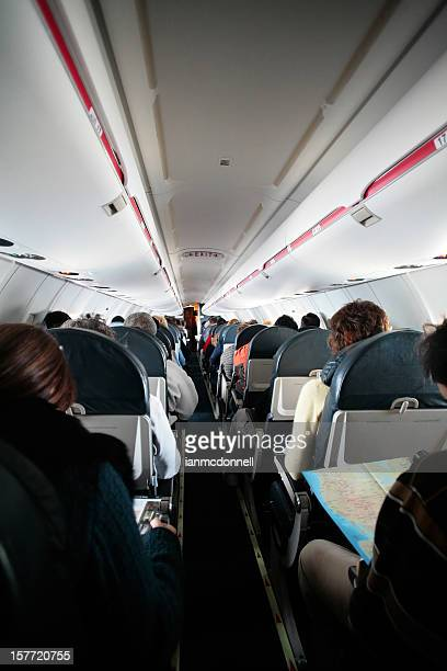 Narrow aisle in an airplane with passengers