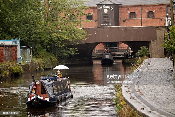 A narrow boat cruises through the rain at Wigan Pier as it makes it's way along the Liverpool and Leeds canal on July 26 2010 in Wigan England A...