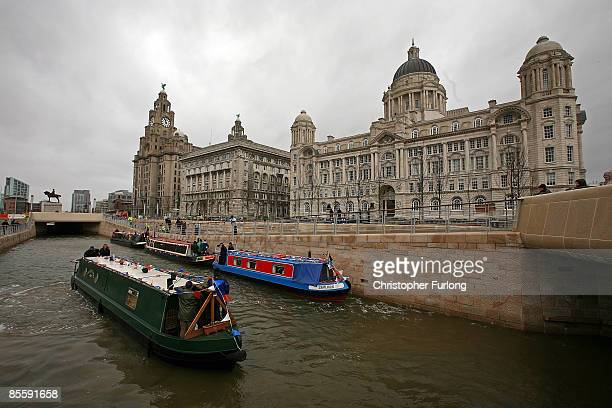 A narrow boat navigates the new stretch of canal in front of Liverpool's 'Three Graces' on March 25 in Liverpool England The new waterway passes the...