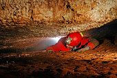 Narrow cave passage with a spelunker explorer