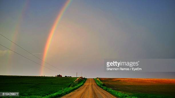 Narrow country road along landscape and against rainbow