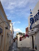 Narrow empty alley along buildings with Greek flag in foreground
