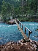 A narrow footbridge crosses over blue glacial water in the Canadian Rockies of British Columbia