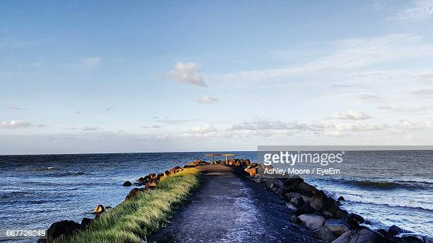 Narrow Pathway Leading To Calm Sea Against Sky