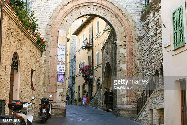 Narrow Street, Arch, Tourists and Stone Buildings, Assisi, Umbria, Italy.