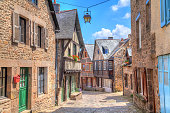 Narrow street with old traditional houses in histoical part of Dinan, Brittany, France