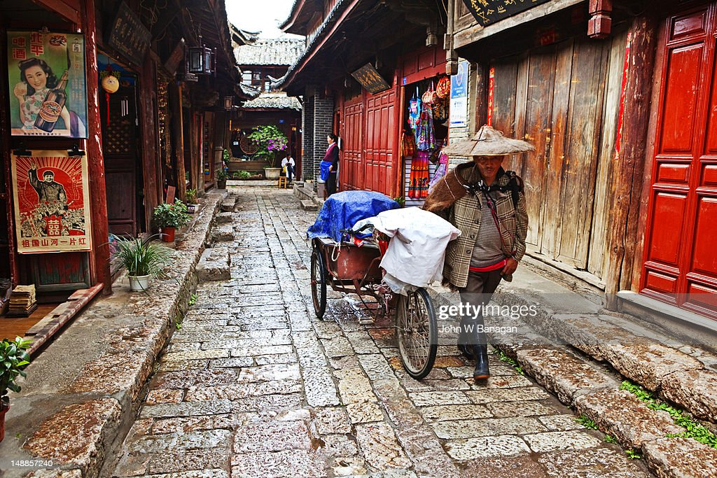 Narrow streets of old town with Naxi man hawker.