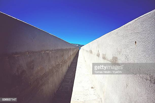 Narrow Walkway Against Clear Blue Sky