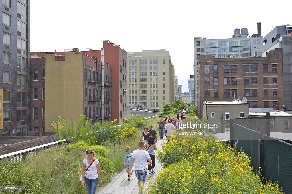 Narrow walkway with people surrounded by flowers