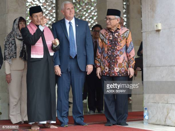 Nasarudin Umar and Muhammad Muzammil Basyuni show the Istiqlal grand mosque to US Vice President Mike Pence in Jakarta on April 20 2017 US Vice...