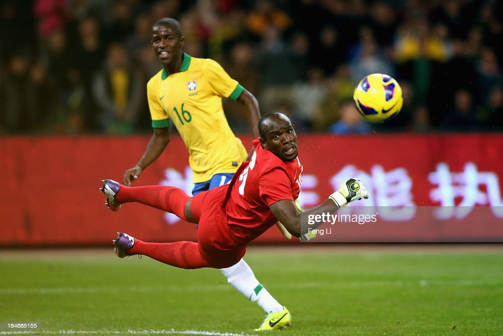 Nascimento Ramires of Brazil (Left) competes the ball with goalkeeper Mweene Kennedy of Zambia (Front) during the international friendly match between Brazil and Zambia at Beijing National Stadium on October 15, 2013 in Beijing, China.