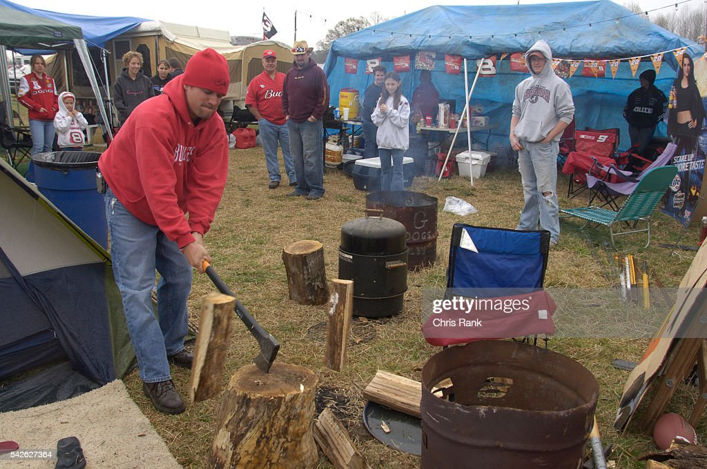 Nash Deaton chops wood for his family while his brother in law Keith Parham looks on at the Atlanta Motor Speedway Most NASCAR racegoers pitch camp...