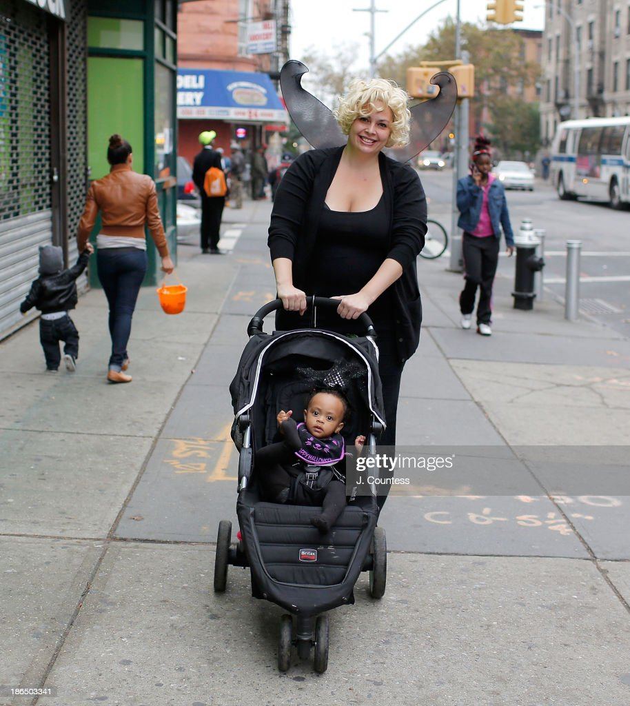Nashon van der Hoop and her daughter pose for a photo in the heart of 'Bedstuy' as they 'Trick or Treat' in Brooklyn on October 31, 2013 in New York City.