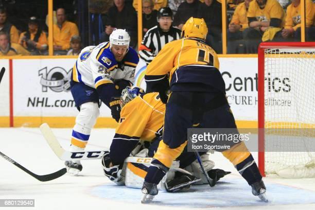 Nashville Predators defenseman Ryan Ellis protects the goal as Nashville Predators goalie Pekka Rinne covers the puck in front of St Louis Blues...