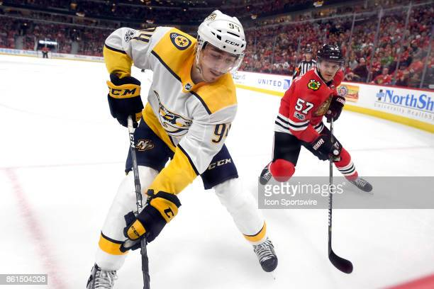 Nashville Predators defenseman Samuel Girard battles with Chicago Blackhawks right wing Tommy Wingels to clear the puck during a game between the...