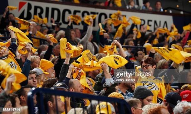 Nashville Predators fans wave their gold towels during an NHL game against the Detroit Red Wings at Bridgestone Arena on February 4 2017 in Nashville...