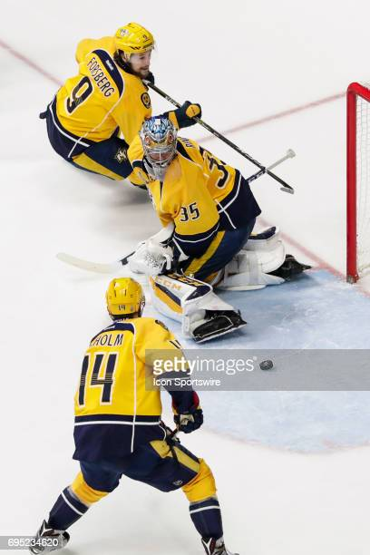 Nashville Predators goalie Pekka Rinne tracks loose puck as Nashville Predators center Filip Forsberg and Nashville Predators defenseman Mattias...