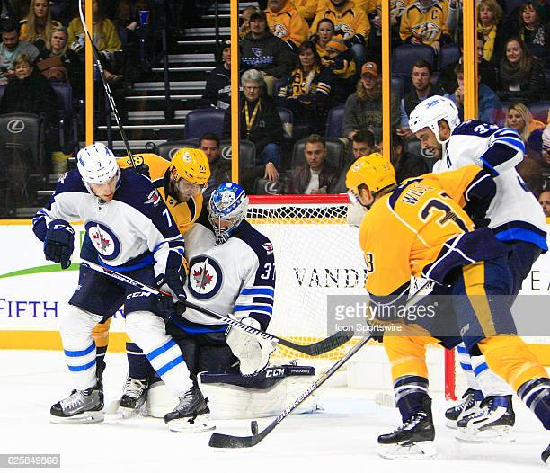 Nashville Predators left wing Colin Wilson and Winnipeg Jets defenseman Dustin Byfuglien pursue the deflected puck as Nashville Predators right wing...