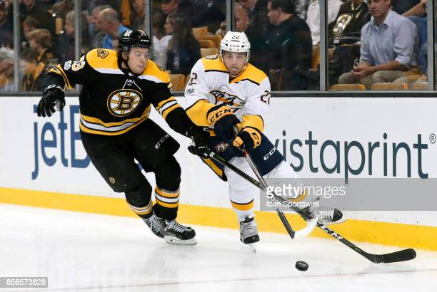 Nashville Predators left wing Kevin Fiala gets the puck back to the point as Boston Bruins right defenseman Charlie McAvoy defends during an NHL game...